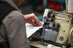 © Licensed to London News Pictures. 21/04/2020. Dukinfield, UK.   A woman  sews medical clothing as staff at Tibard begin working around the clock on an order of 5,000 units of nurses uniforms (scrubs) for NHS workers per week in Dukinfield , owing to growing demand during the COVID-19 pandemic. The factory typically manufactures uniforms for the catering industry.  Photo credit: Ioannis Alexopoulos /LNP