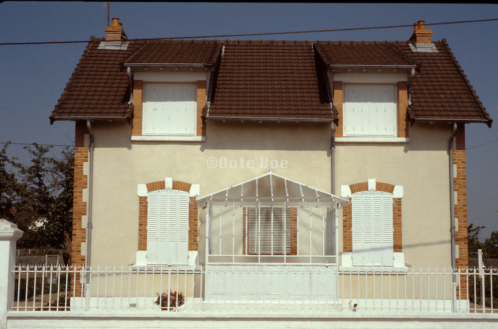 a house in Belgium with the window shutters closed