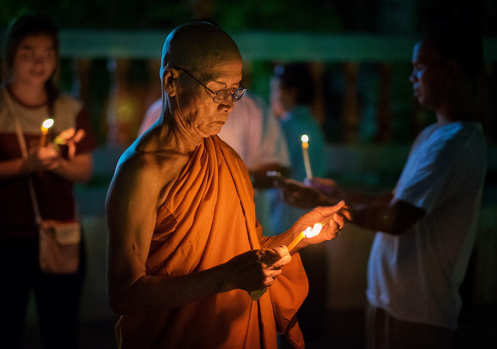 A monk lights a prayer candle during Visakha Bucha Day celebrations, the most important Buddhist holiday of the year in Nakhon Nayok, ‪Thailand‬ May 20, 2016. PHOTO BY LEE CRAKER