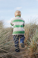 Boy (3-4) walking on path among long grass