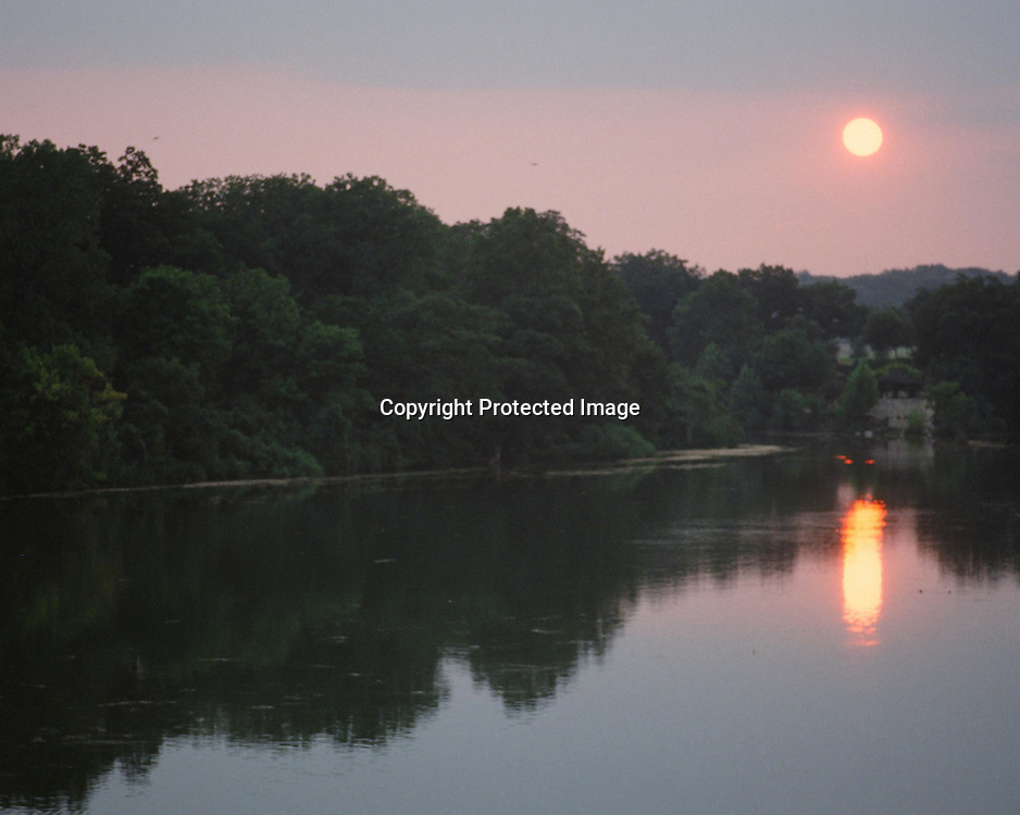 """Sun setting over Lady Bird Lake in Austin, Texas. Horizontal. NOTE: Click """"Shopping Cart"""" icon for available sizes and prices. If a """"Purchase this image"""" screen opens, click arrow on it. Doing so does not constitute making a purchase. To purchase, additional steps are required."""