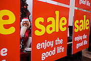 Mannequin of Santa Claus peers between Sale signs in garden retail centre in north Somerset.