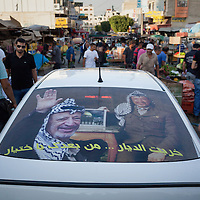 An image of Yasser Arafat, the former leader of Palestinian Liberation Organization, adorns a car driving through a market in Jenin,  the West Bank.