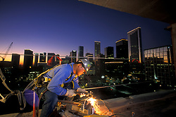 A welder working on the New International Hilton in Houston, Texas with the downtown skyline at dusk.