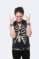 Portrait of young punk man gesturing rock & roll hand sign over white background