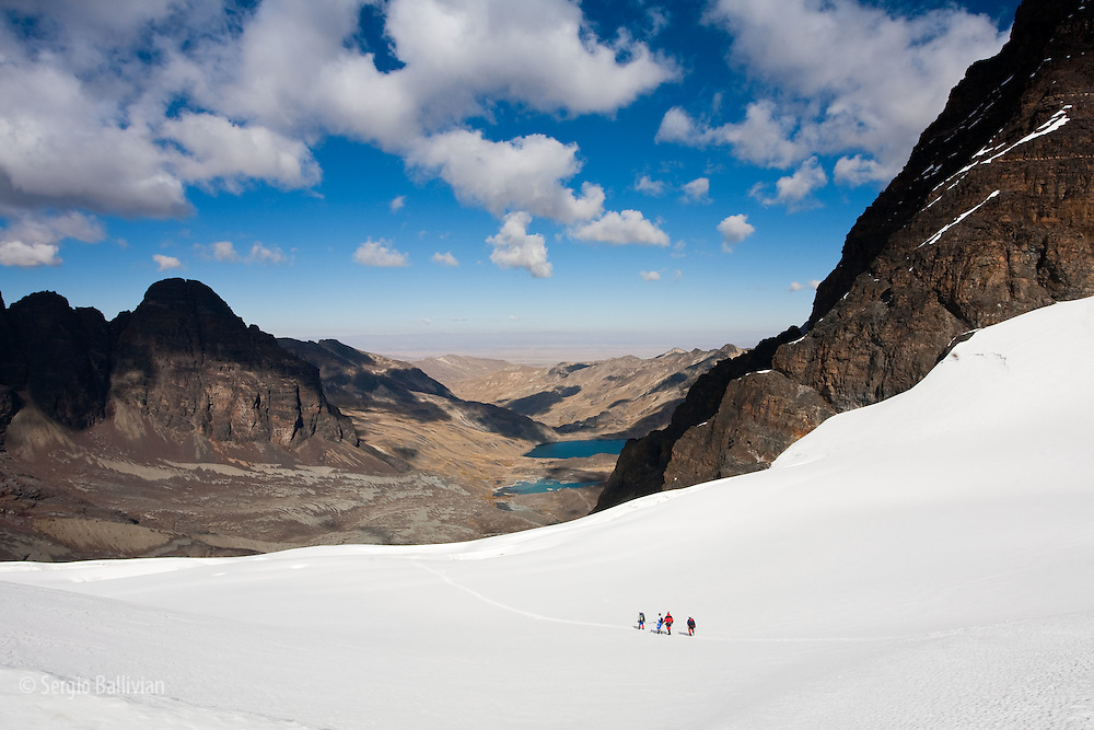 Climbers walk down a glacier towards basecamp and Laguna Chiar Khota after climbing Mt. Pequeno Alpamayo (17,620') in Bolivia's Cordillera Real.