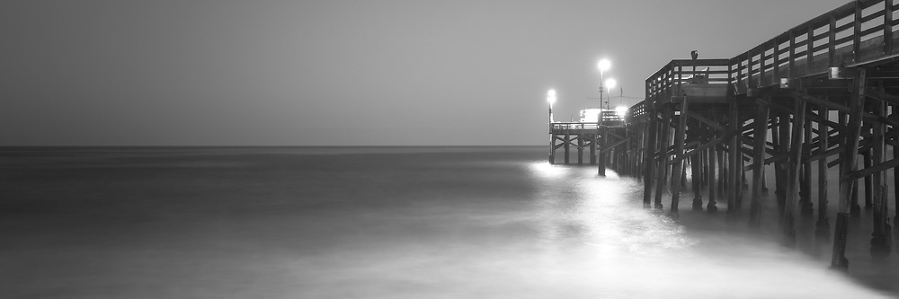 Newport Beach Balboa Pier at night black and white panoramic picture. Newport Beach is a popular coastal beach city in Orange County Southern California.  Copyright ⓒ 2017 Paul Velgos with All Rights Reserved.