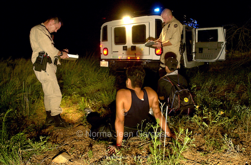 U. S. Border Patrol agents wait for transportation for deportation for illegal immigrants who crossed illegally from Mexico on to the Buenos Aires National Wildlife Refuge near Sasabe, in Arizona, USA.