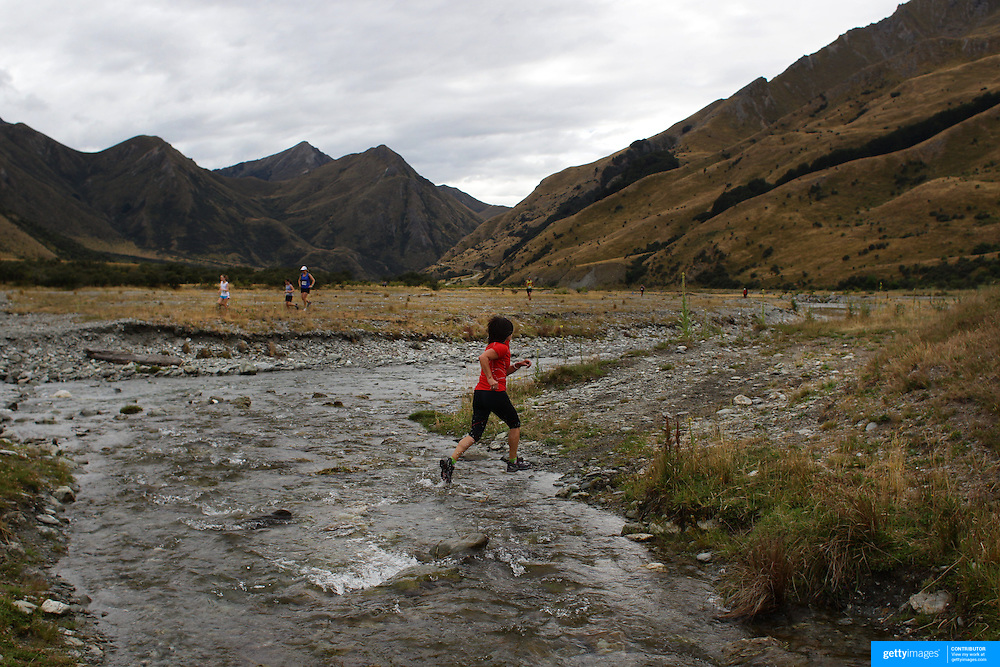 Runner Kelly Elstobb crosses  Moke Creek on the Ben Lomond High Country Station during the Pure South Shotover Moonlight Mountain Marathon and trail runs. Moke Lake, Queenstown, New Zealand. 4th February 2012. Photo Tim Clayton