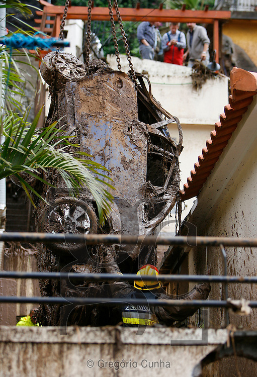 Firefighters lift a car in Funchal, Madeira Island, on February 22, 2010. Residents fled their homes for fear of new mudslides on the tourist island of Madeira Monday as Portugal decreed three days of mourning for the 42 people killed in weekend flash floods. .Photo Gregorio Cunha