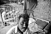 """Tariq, 45 years, in the courtyard of his house. He is the owner of 4 dogs belonging to the family Gullter, a type of mastiff. Suburbs in Rawalpindi, Pakistan, on thursday, August 28 2008.....According to the Islamic tradition, angels do not enter a house which contains dogs. Even if they are considered """"ritually unclean"""" by the jurists, the fighting dogs of Pakistan are tolerated by institutions and by believers alike. These mastiffs are grown and trained explicitly for these matches. Spectators in this area flock-in from nearby villages whenever a famous dog is scheduled to enter the arena. And this is more than just a show: entire families base their social esteem on the results of such bloody confrontations."""