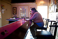 A woman drinks alone in a bar at noon. <br /> Alcoholism is a big problem in Detroit with people escaping into drinking, hoping to forget their problems. The economic crisis has increased these issues. New legislation starting in October 2011, cutting people off benefits who have been unemployed for over 2 years, will increase the problems even further. Detroit, USA, 2011