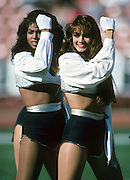 Two Los Angeles Raiders cheerleaders perform during the NFL football game between the New England Patriots and the Oakland Raiders on November 26, 1989  in Los Angeles, California. The Raiders won the game 24-21. ©Paul Anthony Spinelli