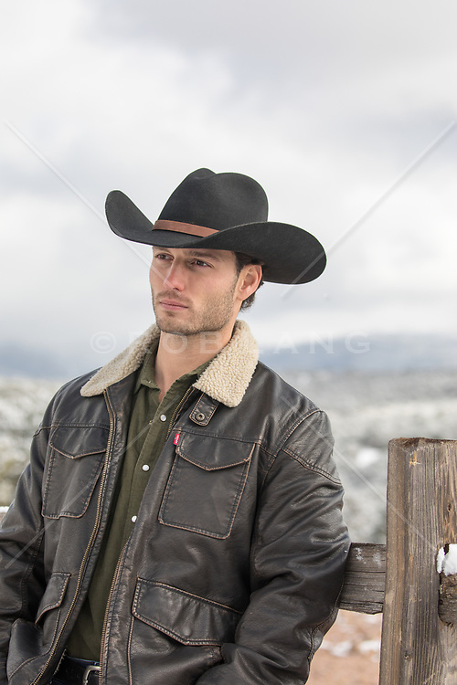 cowboy by a spilt rail fence in Winter