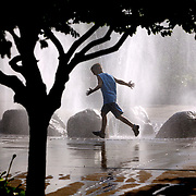 A child keeps cool at the 2008 Iowa State Fair in Des Moines, Iowa, by running through a fountain of misty water.  The fair set attendance records this year, as temperatures stayed in the 80's, unusual for August.