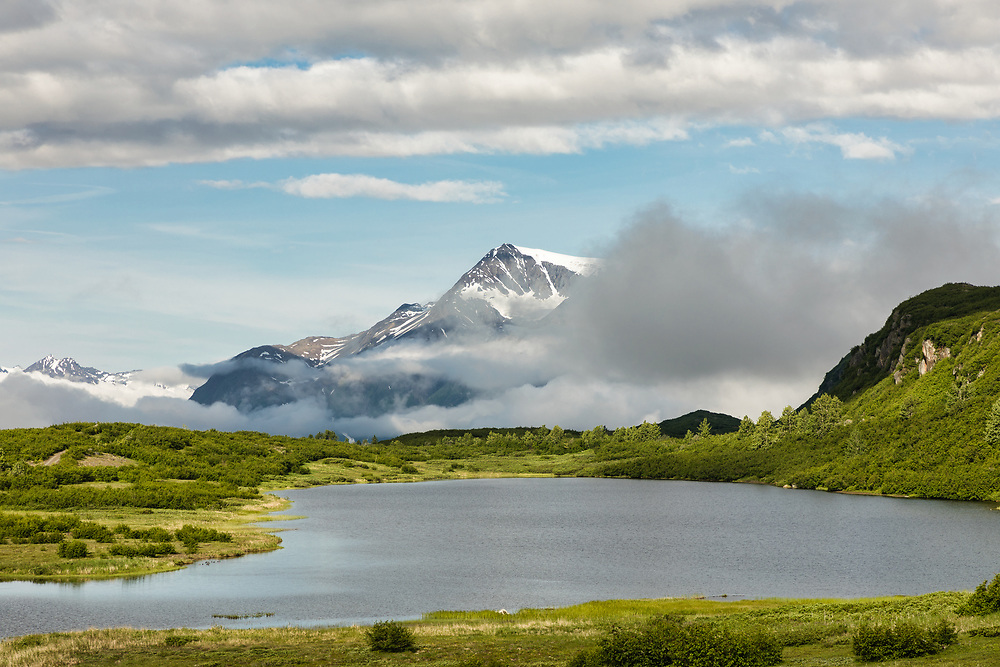 Clouds part in Thompson Pass to reveal Hogback Glacier near Valdez in Southcentral Alaska. Summer. Morning.