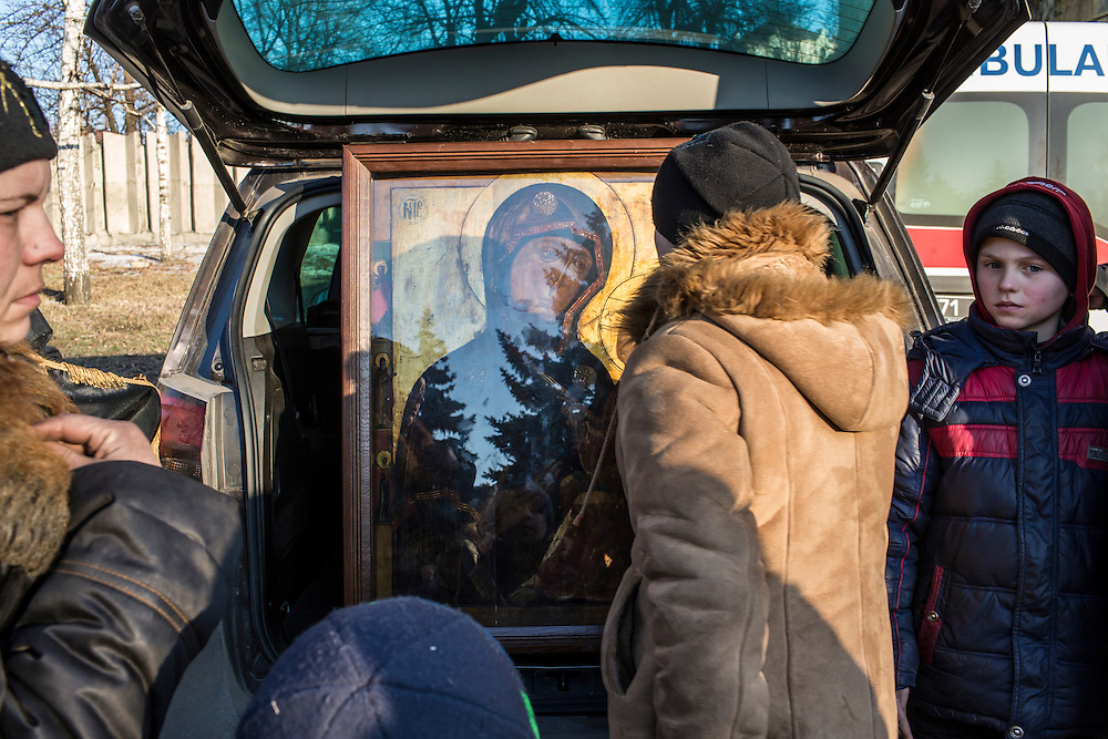 DEBALTSEVE, UKRAINE - FEBRUARY 20: Local residents pray at a religious icon displayed on the central square on February 20, 2015 in Debaltseve, Ukraine. Ukrainian forces withdrew from the strategic and hard-fought town after being effectively surrounded by pro-Russian rebels, though fighting has caused widespread destruction. (Photo by Brendan Hoffman/Getty Images) *** Local Caption ***