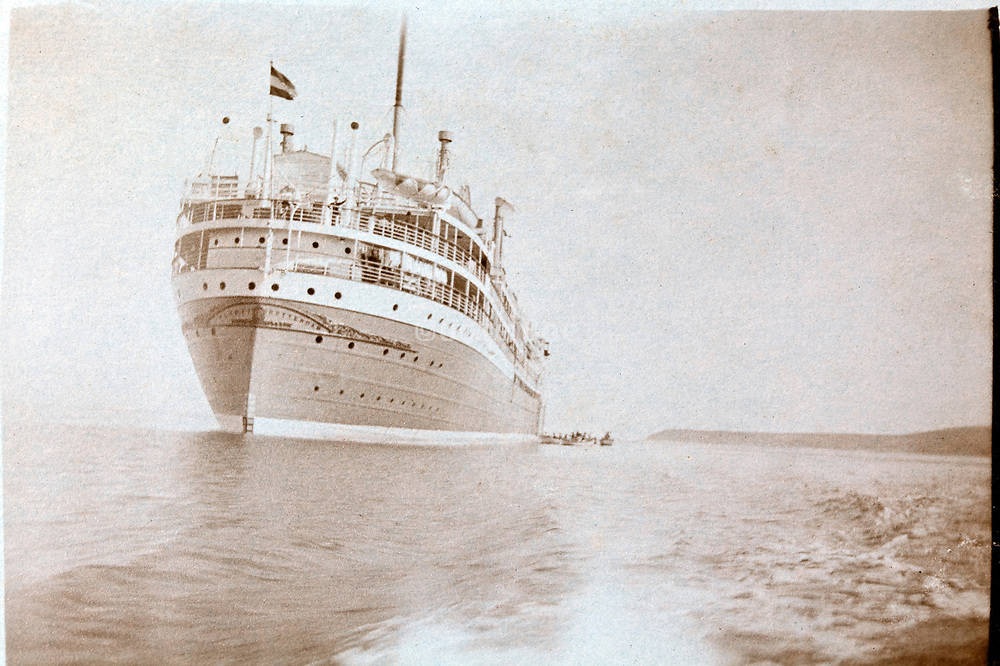 a large cruise passenger ship by the coast of Morocco with a waving passenger 1930s