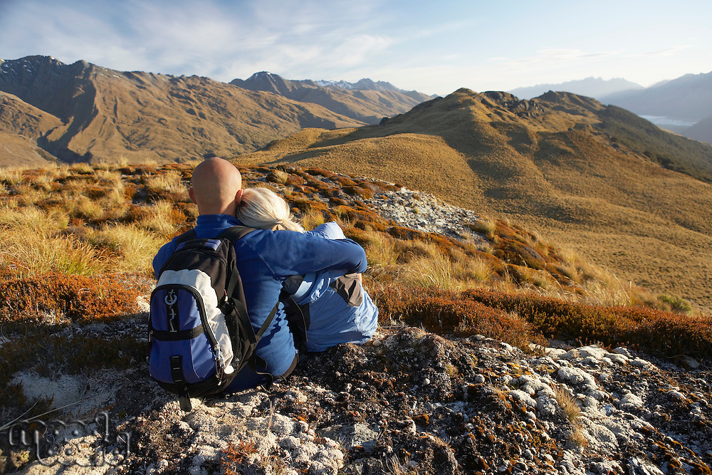 Couple embracing looking at hills back view