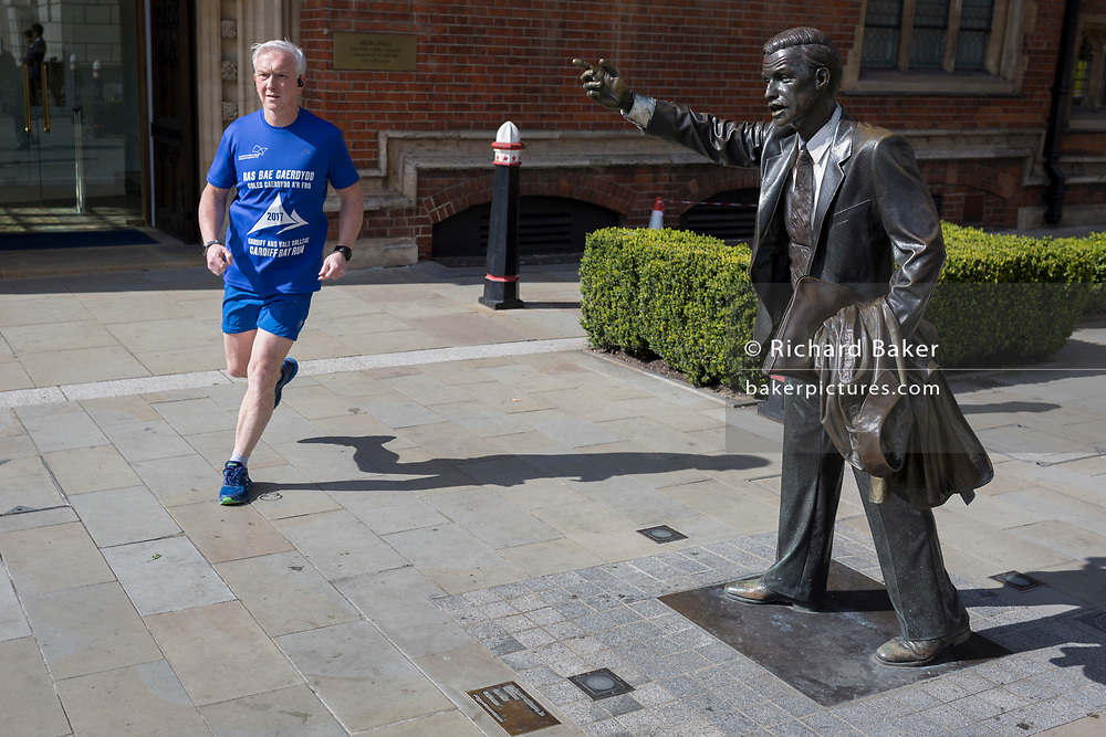 A runner passes-by the sculpture of artist John Seward Johnson, entitled 'Taxi!' (1983) on John Carpenter Street in the City of London, the capital's financial district, on 25th March 2019, in London, England.