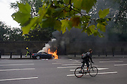 A cyclist pedals past a Mercedes as it burns at the side of the road at Hyde Park Corner in central London.