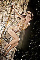 Body painted nude model posing on tile mosaic in pinup pose.