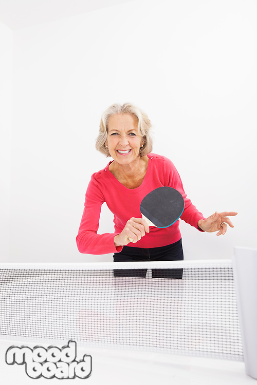 Portrait of happy senior woman playing table tennis