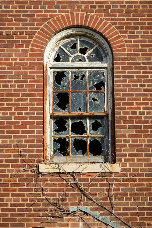 Broken window panes on old brick building in Glen Dale, Maryland
