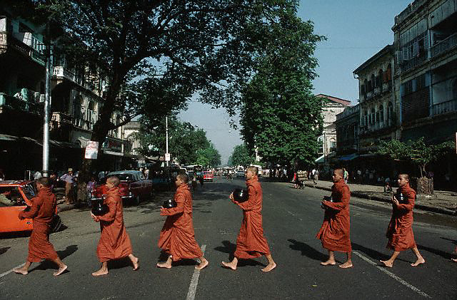 1985, Yangon, Myanmar --- Several Buddhist monks cross a street in Yangon. They are going on their morning begging rounds. --- Image by © Owen Franken/CORBIS