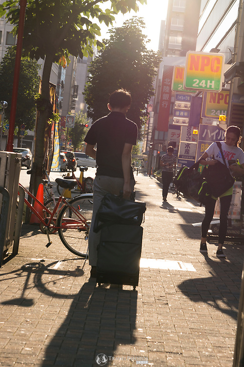 A man dragging a suitcase in the late afternoon through the trendy Sakae district of Nagoya Japan.