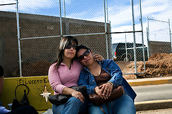Two sisters wait at a Mexican customs and immigration office. Many returned immigrants pass through this point and the sister received a call that a family member had been detained for entering the US illegally and was being repatriated to Mexico.