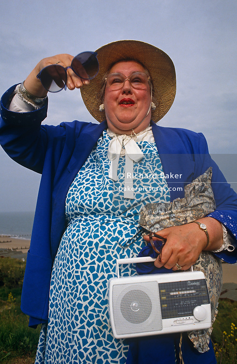 From a low angle we see, waving a cheery hello to a friend, a rather plump resident of the posh Essex seaside town of Frinton-on-Sea holds on to her oversized sunglasses, her cushion and a portable transistor radio - all of which she has been using whilst on the sea front that we see in the distance behind her round body. Wearing 'Tory blue' (the colour favoured by the Margaret Thatcher during the eighties) the lady has her straw hat tied under the folds of fat of an ample chin and appears to be calling an English Coo-ee! call to the out-of-sight acquaintance.