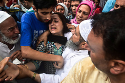 June 15, 2018 - Baramulla, J&K, India - Relatives console a wife of Shujaat Bukhari, veteran journalist and Editor-in-Chief of English daily 'Rising Kashmir,' during a funeral procession  in Kreeri, some 45kms from Srinagar, Indian administered Kashmir. Thousands of mourners attended Shujaat Bukhari's funeral in Baramulla today. Bukhari and his personal security officers (PSO's) were shot dead by unidentified gunmen at Press Colony in Srinagar on Thursday evening. (Credit Image: © Saqib Majeed/SOPA Images via ZUMA Wire)