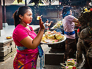 11 OCTOBER 2016 - UBUD, BALI, INDONESIA: A woman sprinkles water during her prayers at the Hindu temple in the market in Ubud. The temple in the market is very busy during the midmorning hours, when market vendors come to pray. The morning market in Ubud is for produce and meat and serves local people from about 4:30 AM until about 7:30 AM. As the morning progresses the local vendors pack up and leave and vendors selling tourist curios move in. By about 8:30 AM the market is mostly a tourist market selling curios to tourists. Ubud is Bali's art and cultural center.      PHOTO BY JACK KURTZ