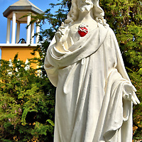Christ Statue in Front of Church Tower in Kralendijk, Bonaire <br /> A group of Dutch Catholic nuns began a school here in 1856. In 1922, the Sisters of Roosendaal established the San Francisco Hospital. Eight years later, they dedicated this Christ statue. The inscription reads, &ldquo;Sacred Heart of Jesus, I Trust in You.&rdquo; In 1957, a humble chapel with a bell tower was constructed. These are now part of the Mariadal Foundation campus of medical facilities, the largest on the island.