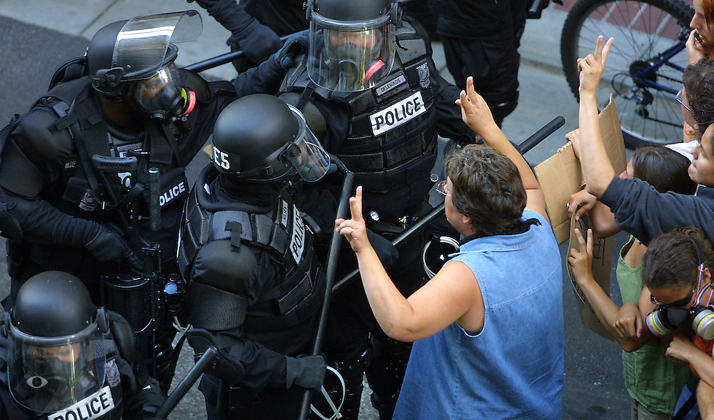 A peaceful protestor in Portland attempts to keep riot police from moving foreward, thus inciting the crowd. A visit by President George W. Bush sparked a backlash of anger about his politics.