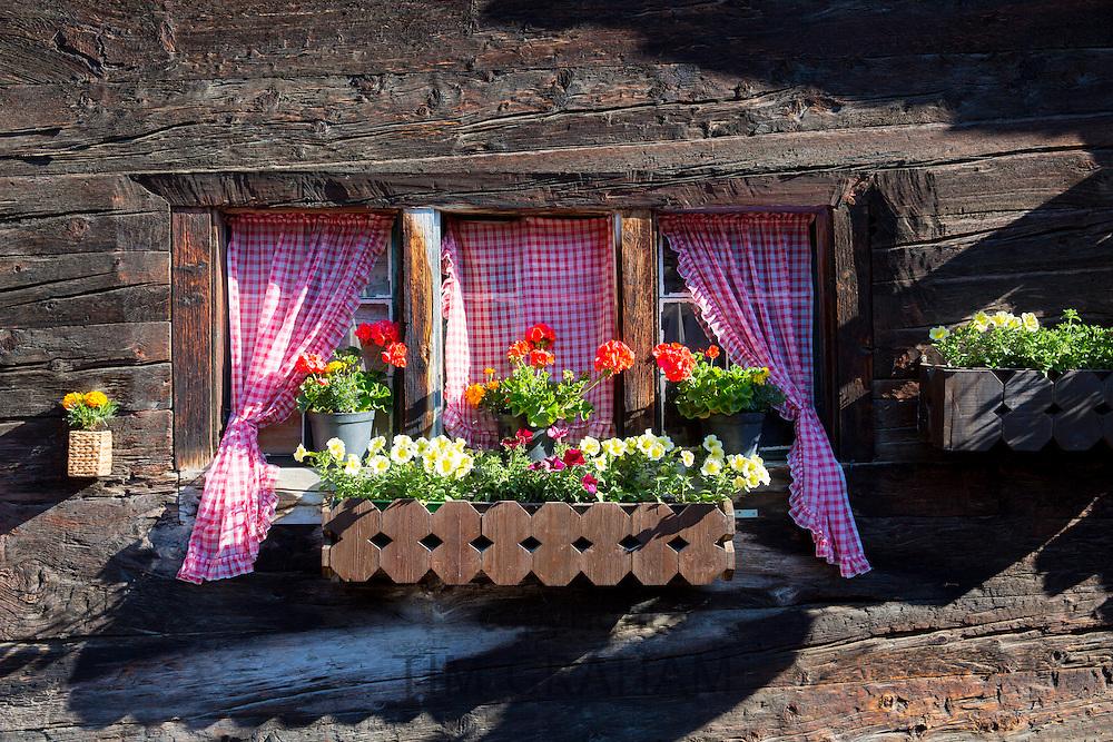 Traditional window of chalet in village of Zmutt in the Swiss Alps near Zermatt, Switzerland