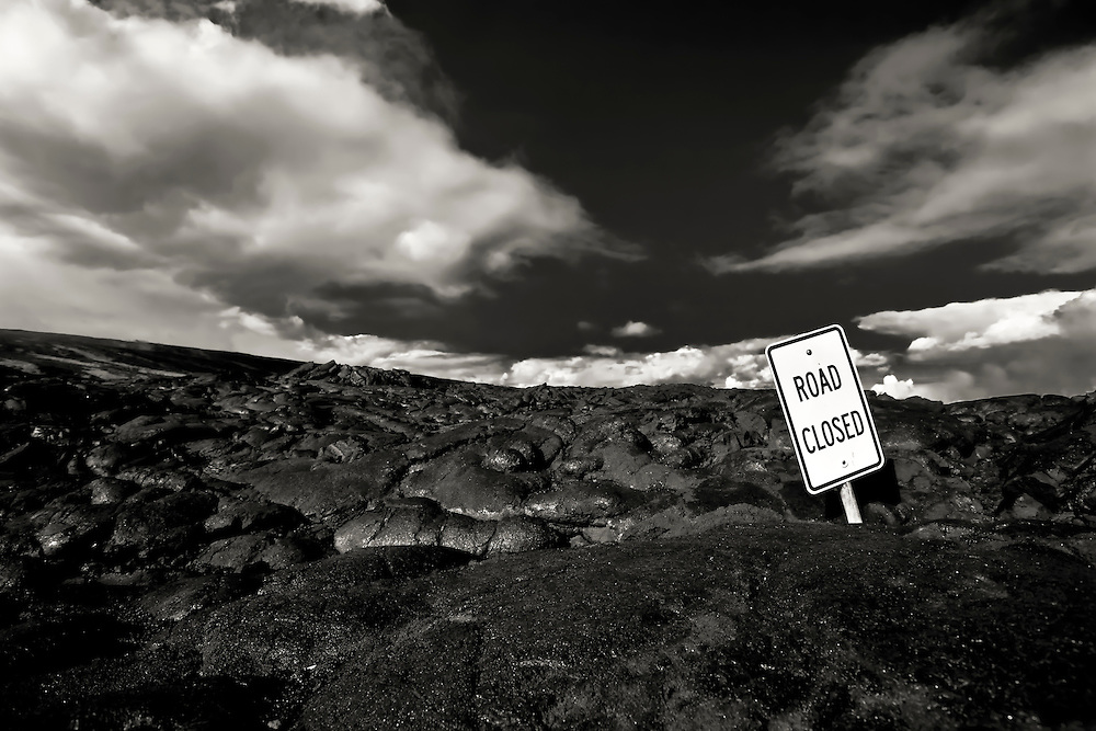 Hardened lava flow covers road at southwestern part of Hawaii, but luckily not the sign.  Copyright 2008 Reid McNally.