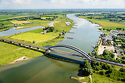 Nederland, Gelderland, Culemborg, 26-06-2014. Rivier de Lek en spoorbrug Culemborg (Kuilenburgse spoorbrug). In de Goilberdingerwaard en Baarsemwaard (links) is de zomerdijk verlaagd en gedeeltelijk weggegraven en ook zijn in de uiterwaard geulen gegraven om rivier de Lek bij hoogwater meer de ruimte te geven. Railway bridge Culemborg and Lek River. In the floodplains (left) the summer dike has been reduced in height and partially excavated, and trenches haven been dug to create 'room for the river' at heigh waters.<br /> luchtfoto (toeslag op standard tarieven);<br /> aerial photo (additional fee required);<br /> copyright foto/photo Siebe Swart
