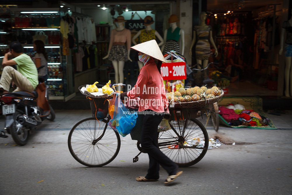 15/04/2013 - Hanoi, Vietnam. A female street vendor selling fresh pineapple from her bicycle. Photo by Rob Arnold