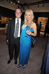AZAD & NATALIA COLA owners of The Westbury hotel at a party to celebrate the publication of Elena Makri Liberis's book 'Every Month, Same day' held at Sotheby's, 34-35 New Bond Street, London on 5th May 2009.
