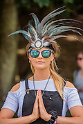 A womanin a feathered head-dress, enjoys the Yoga class on the waterfront stage - The 2016 Latitude Festival, Henham Park, Suffolk.