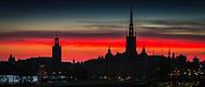 Stadshuset och Riddarholmskyrkan i siluett mot röd solnedgångshimmel i Stockholm