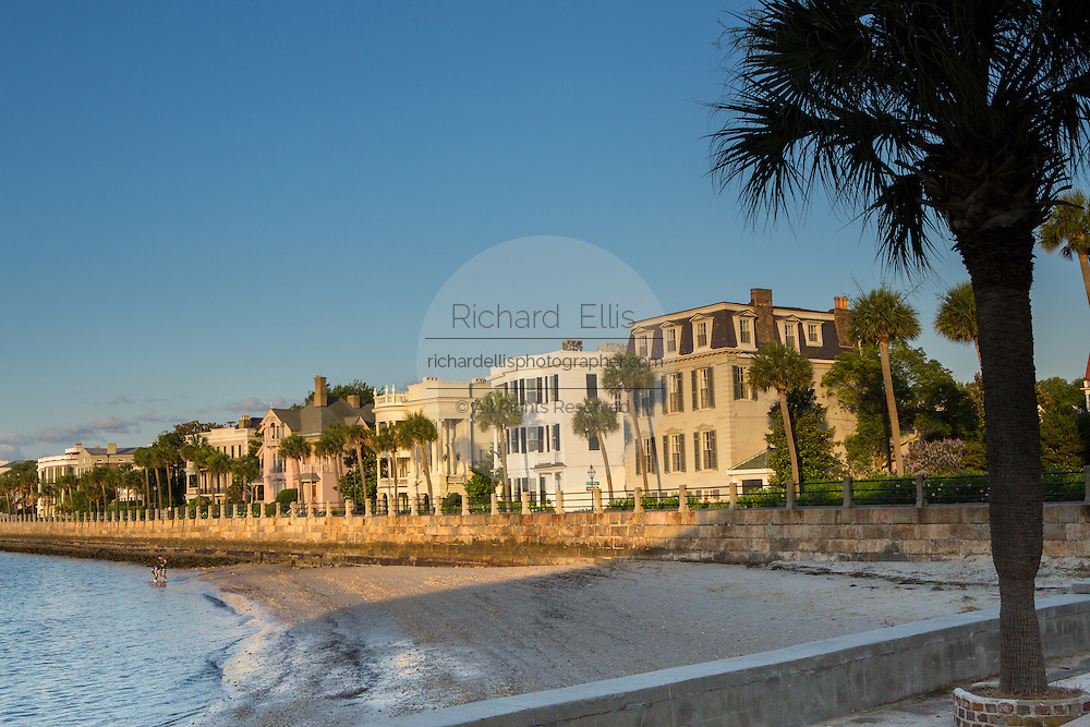 A young couple walks along the beach past stately antebellum historic homes along the High Battery in Charleston, SC.