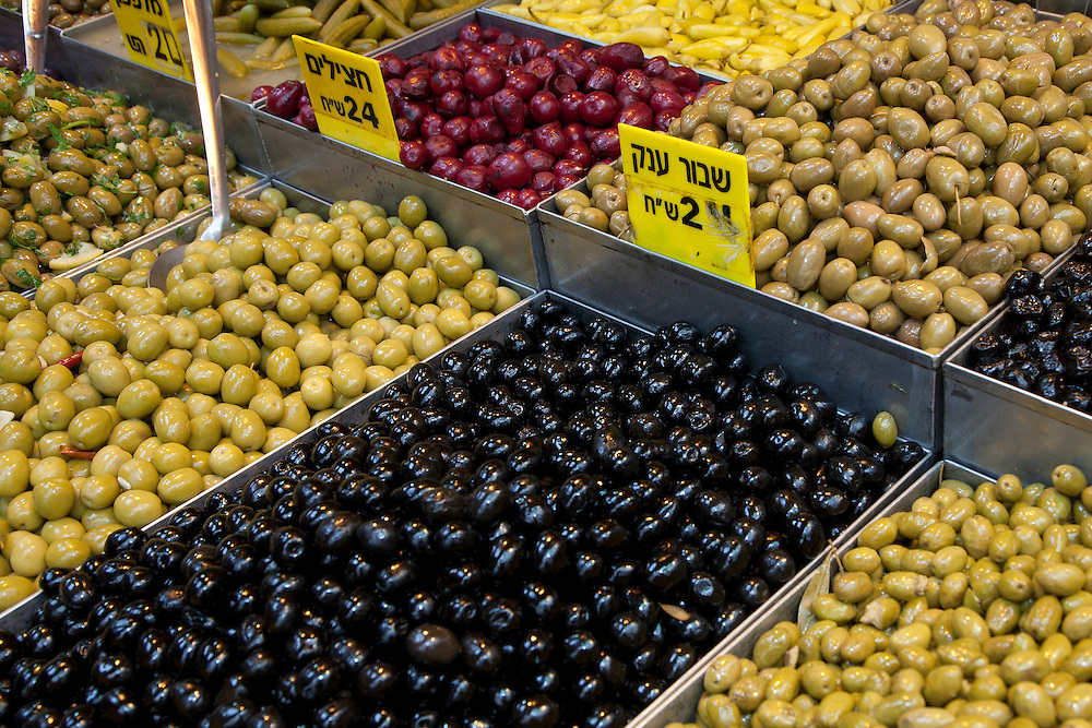 """Middle East, Israel, Jerusalem,  olives on display at Mahane Yehuda Market (also known as Machaneh Yehuda), often referred to as """"The Shuk"""", is popular with locals and tourists alike, the market's more than 250 vendors sell fresh fruits and vegetables; baked goods; fish, meat and cheeses; nuts, seeds, and spices; wines and liquors; clothing and shoes; housewares, textiles, and even Judaica."""