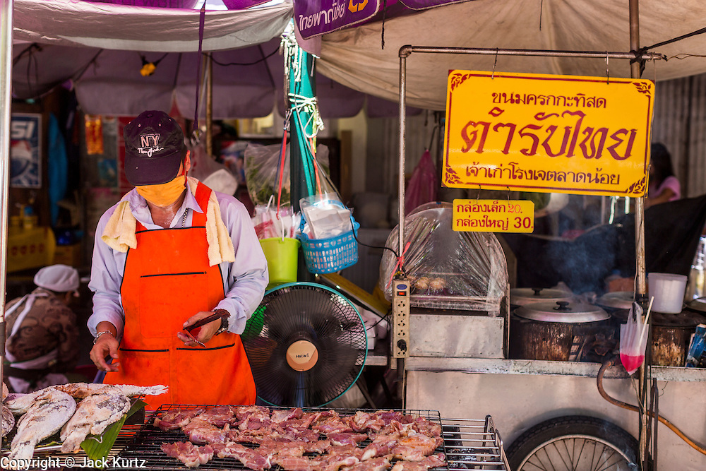 26 APRIL 2013 - BANGKOK, THAILAND:    A grilled meat and fish street food vendor in Talat Noi. The Talat Noi neighborhood in Bangkok started as a blacksmith's quarter. As cars and buses replaced horse and buggy, the blacksmiths became mechanics and now the area is lined with car mechanics' shops. It is one the last neighborhoods in Bangkok that still has some original shophouses and pre World War II architecture. It is also home to a  Teo Chew Chinese emigrant community.      PHOTO BY JACK KURTZ