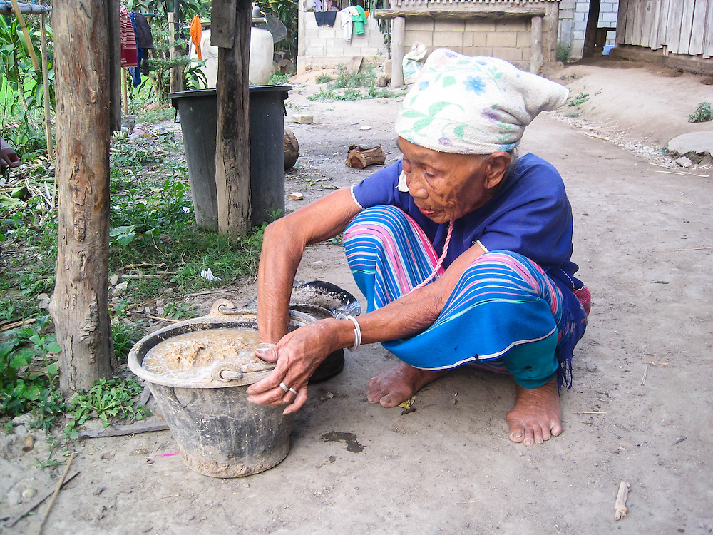 This is Mida's grandmother's friend Suh luh Pee. She is cooking for her pigs. Mida enjoys taking photographs of life in her village.