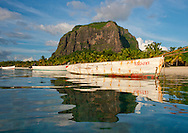 An old wooden fishing boat and watery reflections of Le Morne Brabant on Le Morne Brabant Peninsula on the south west coast of Mauritius;  The Indian Ocean