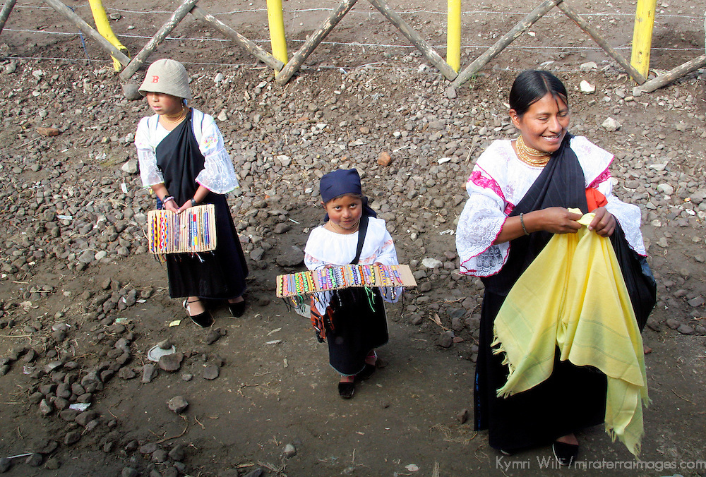 South America, Ecuador, Otavalo. A woman raises her daughters to learn the art of roadside vendorship in the Andes of Ecuador.