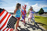 Aaliyah Malay leads the front of a parade carrying the flag as Shawn Toles, center, and Kali Warner wait to finish the route Friday during the 8th annual Cottage Childcare and Learning's Fourth of July parade.